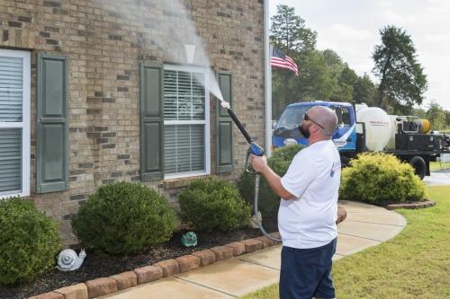 man power washing a brick house