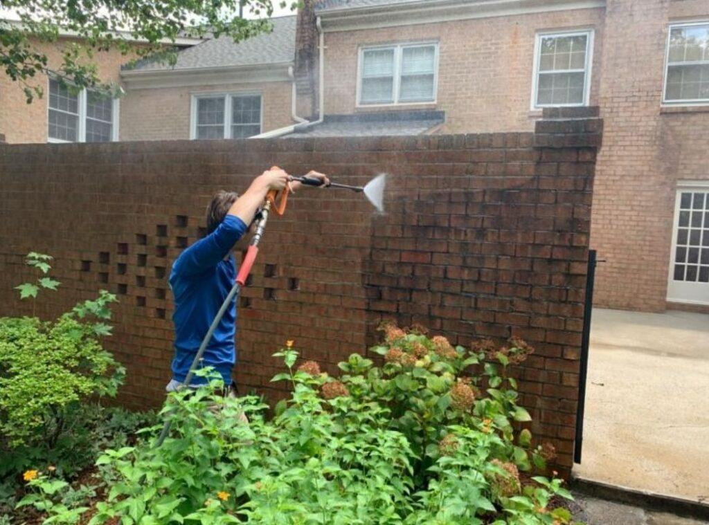 Carolina Power Wash employee power washing brick wall