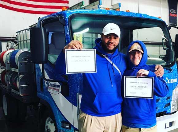 Two Carolina Power Wash employees holding up certificates